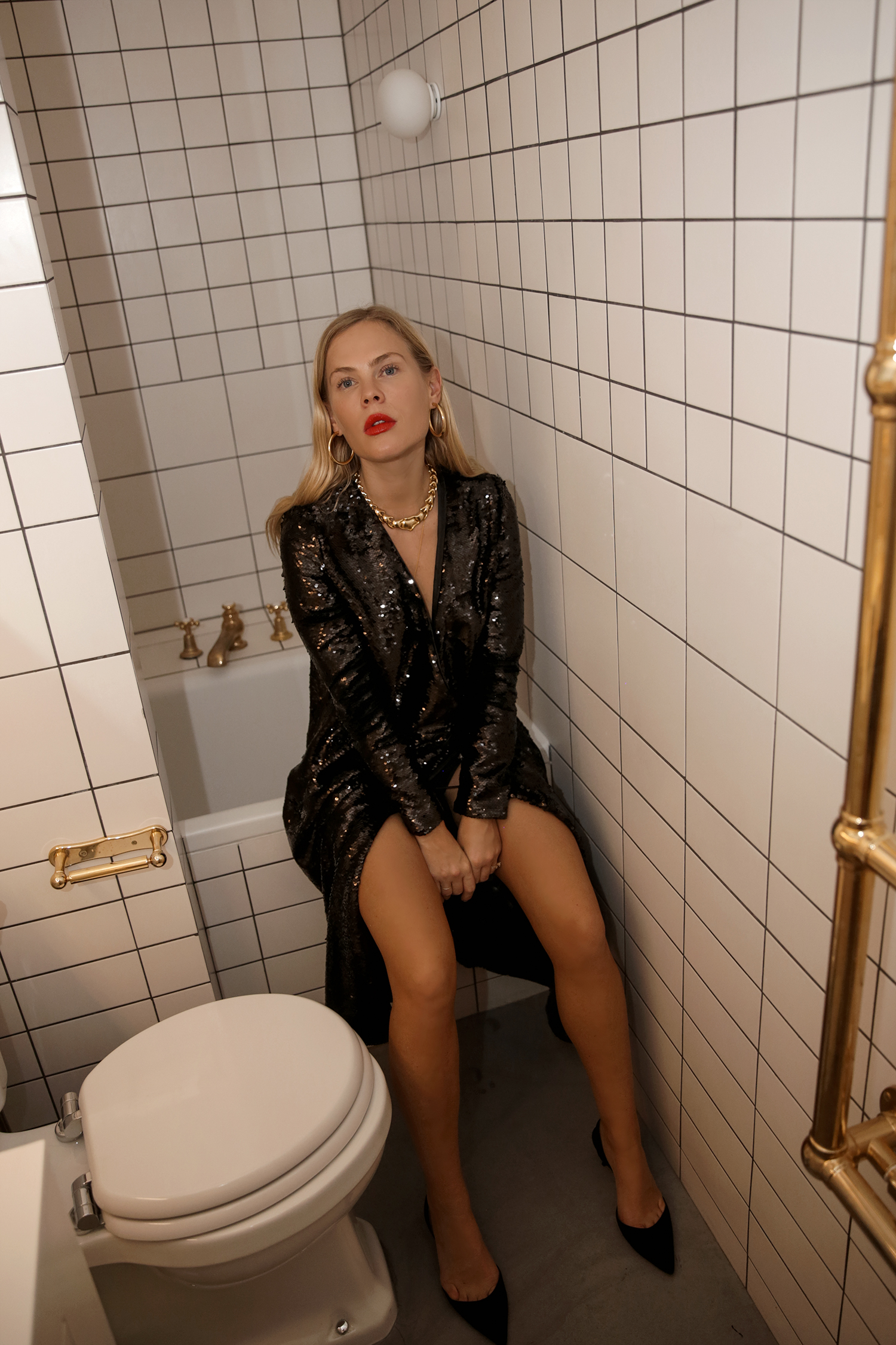 Girl sitting bathroom sequins black heels gold necklace makeup